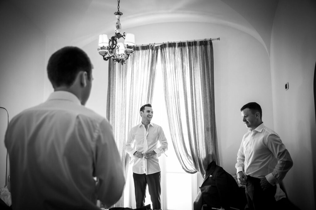 groom getting ready with best men in hotel room in ravello