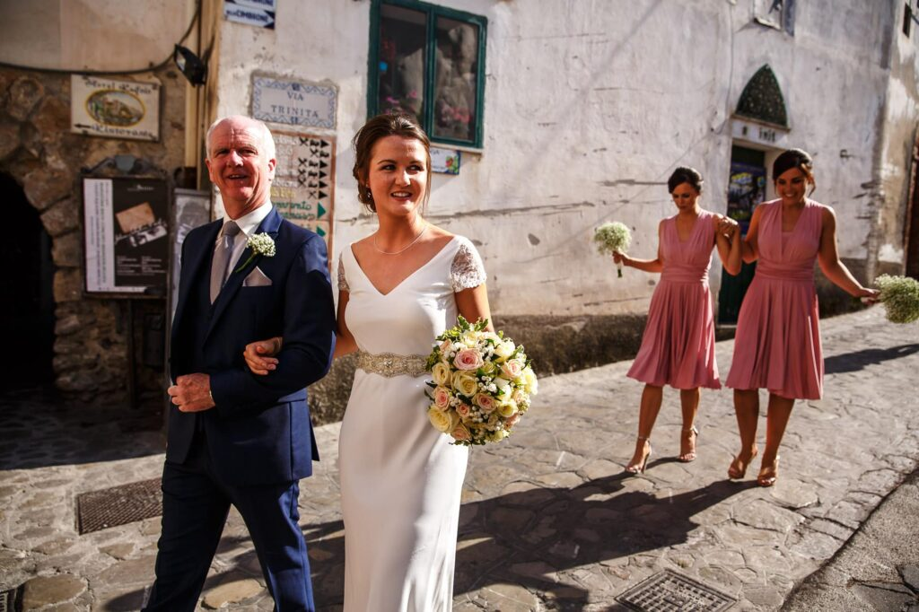 bride walling with dad and bridesmaid in ravello
