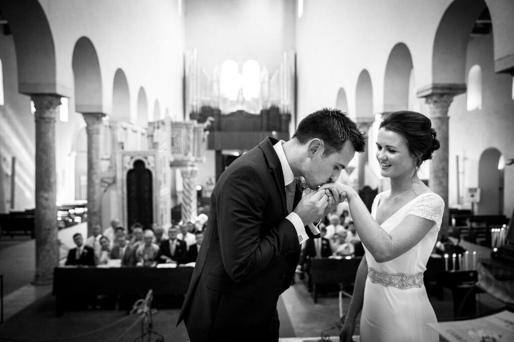 the groom kisses the bride hand upon her arrival in the cathedral of ravello
