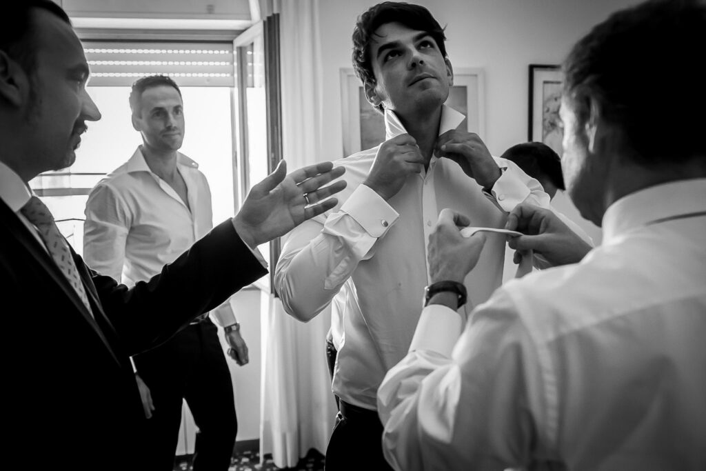 groom getting dressed with friends and witnesses for his summer wedding in rome