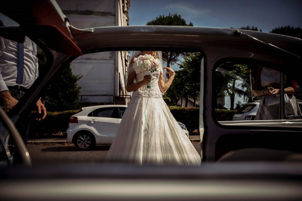 bride leaving home and getting into the car to go to the relaxed summer wedding in rome