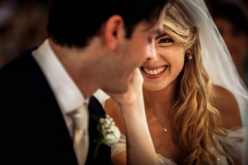 smiling bride caresses groom during summer wedding in rome