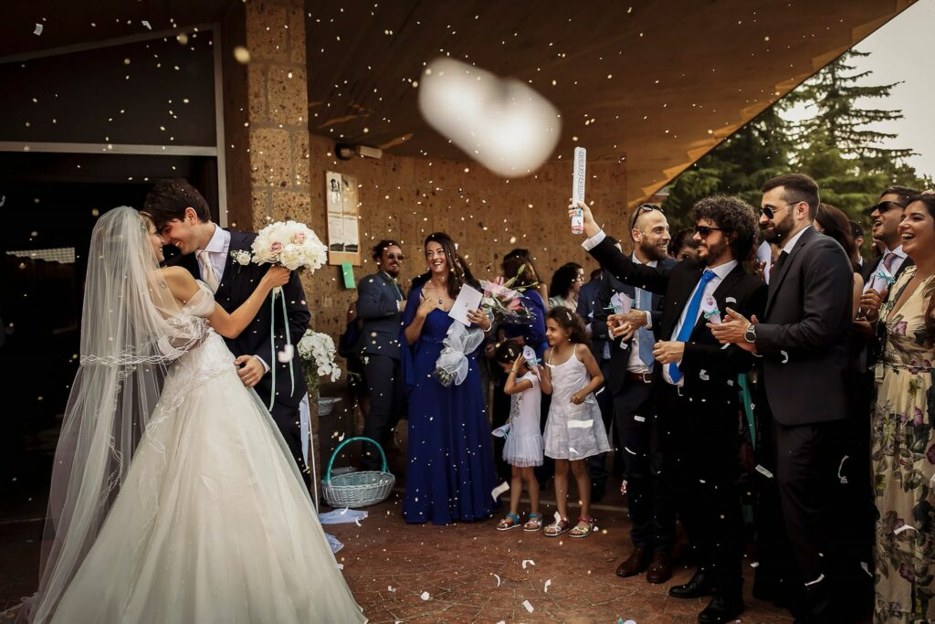bride and groom exiting the church and facing confetti throwing