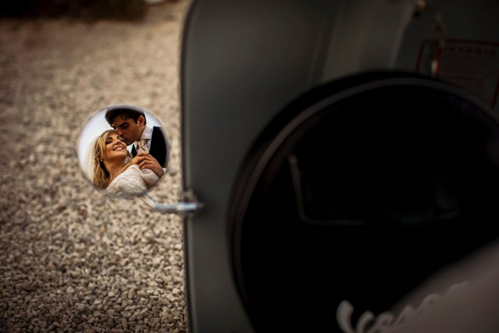 portrait of the bride and groom taken in the mirror of the vespa