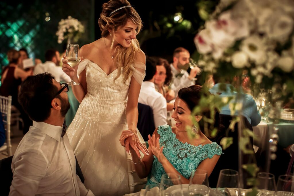 bride showing wedding ring to a friend during the summer wedding dinner in rome