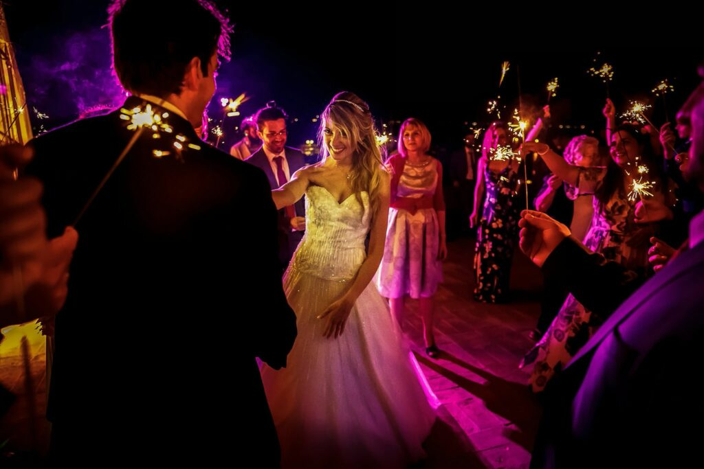 bride and groom first dance amongst guests with sparklers at wedding reception