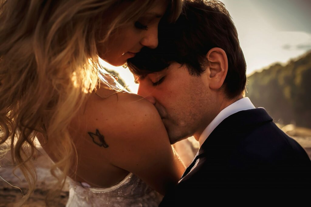 groom kissing bride shoulder with tattoo in rome