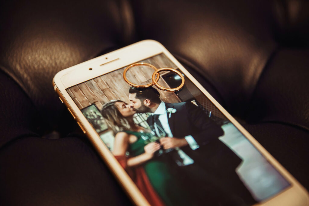 detail of the wedding rings over an iphone dislaying a photo of a kissing couple