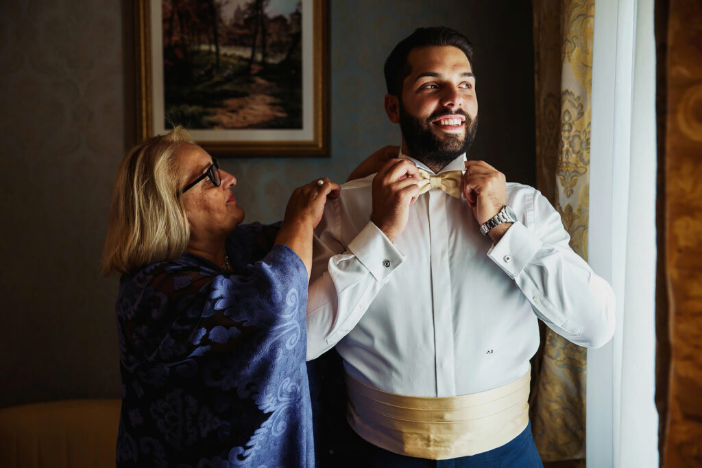 groom getting dressed with the help of his mother