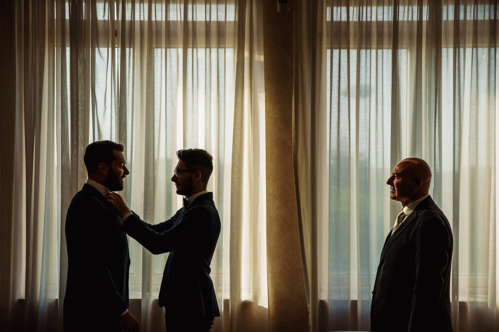 groom getting dressed with the help of his best man and his father