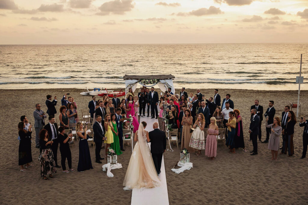 arrival of the bride at the ceremony of the beach wedding by the sea at sunset