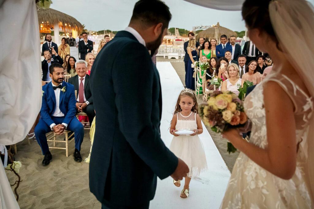 little bridesmaid bringing wedding rings to bride and groom at their beach wedding at la rambla