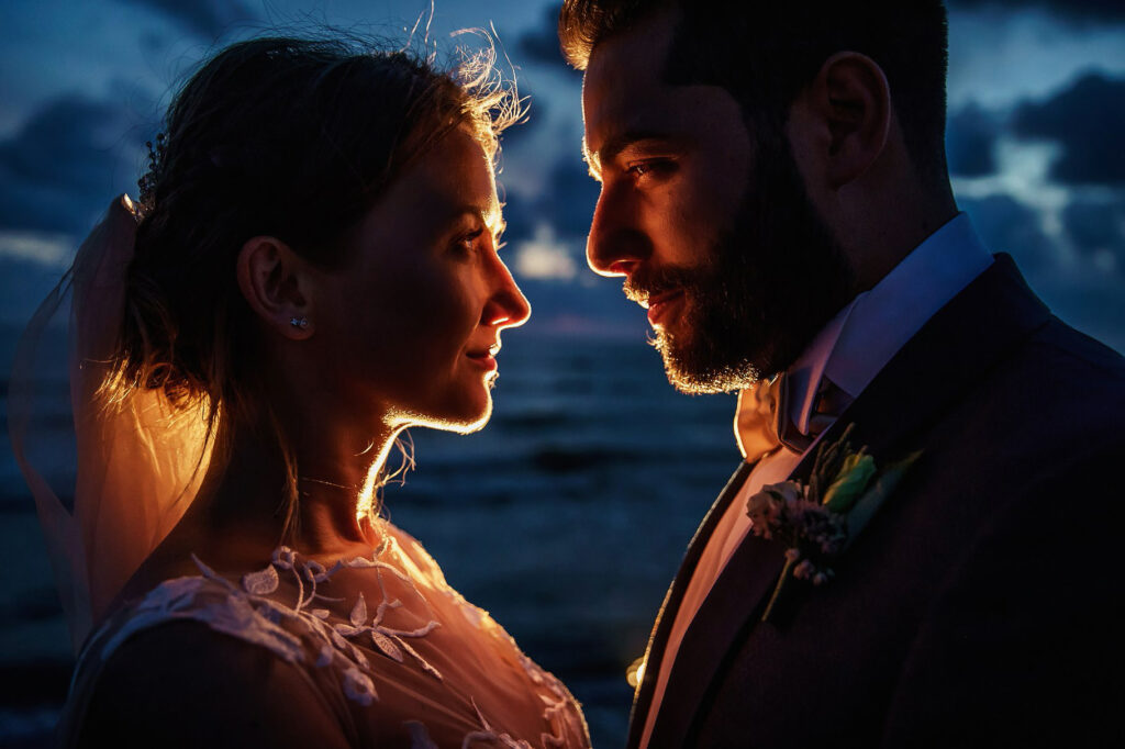 couple portrait on the beach at sunset after the ceremony bride and groom looking in each other eyes