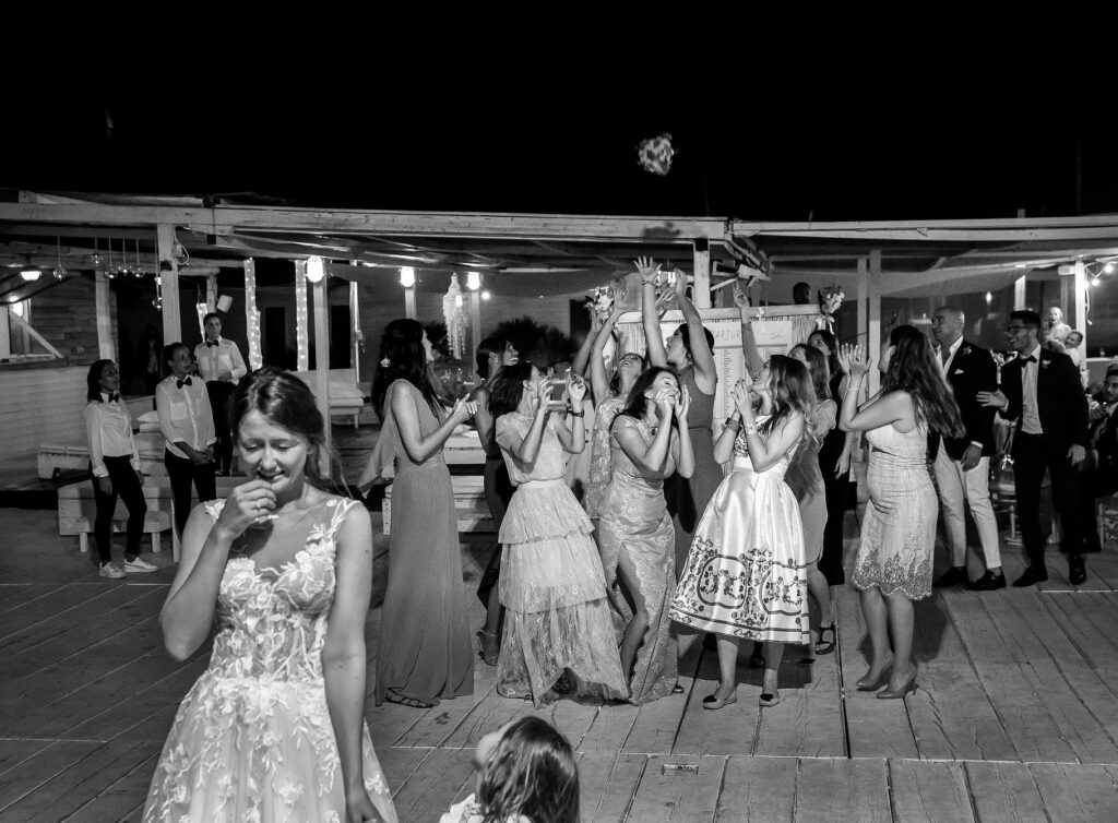 bride throwing bouquet after the beach wedding