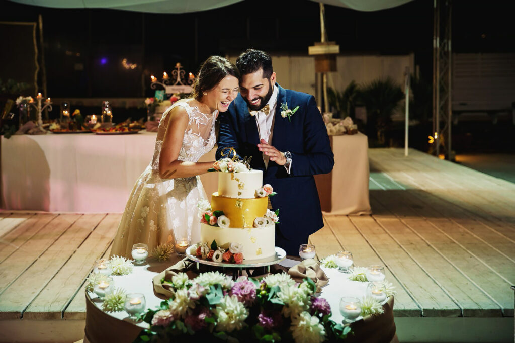 bride and groom cutting the cake at the beach wedding