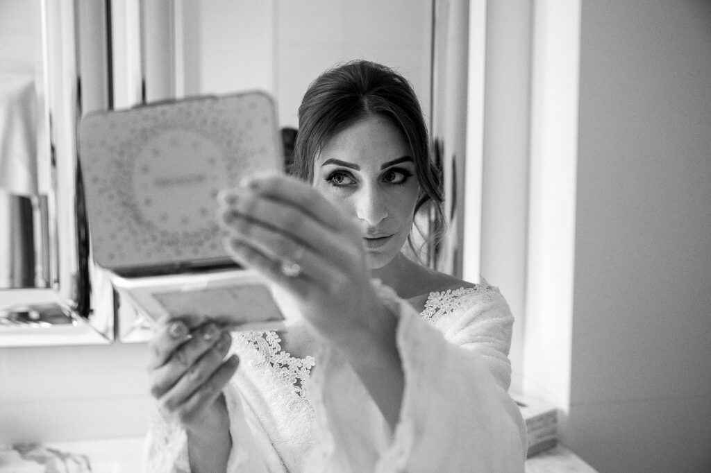 bride checking her make-up at gettin ready for her wedding in paris