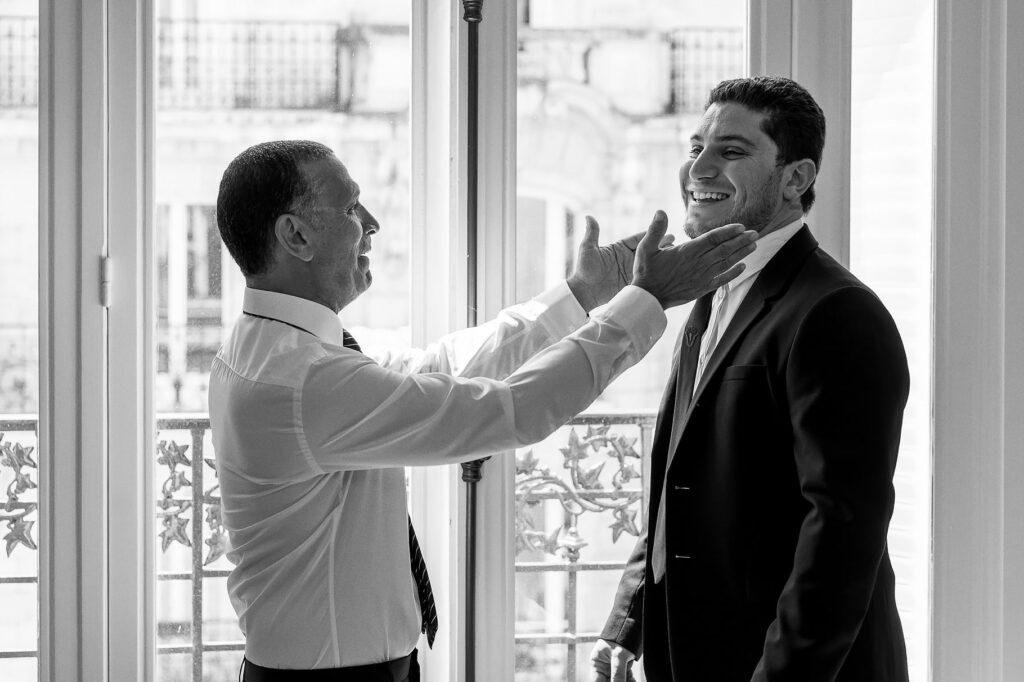 the brother and father of the bride joking near the window