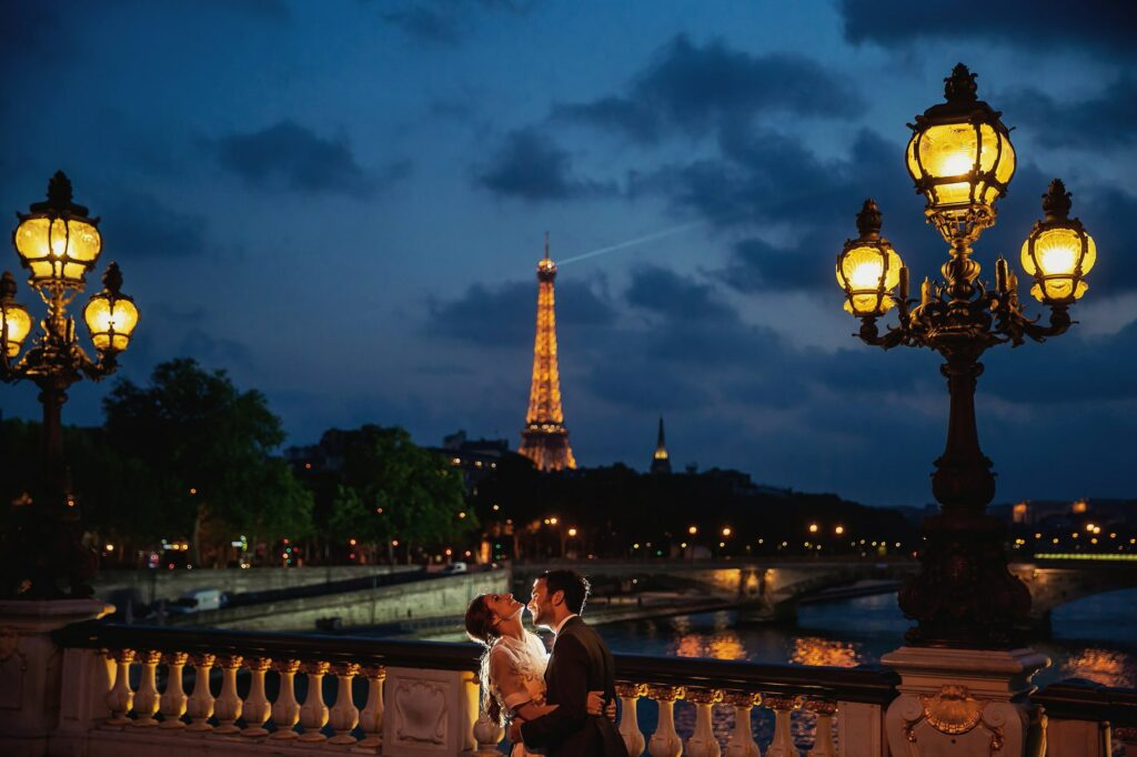 bright and groom hugging at sunset on the bridge pont des invalides with the tour eiffel in the background