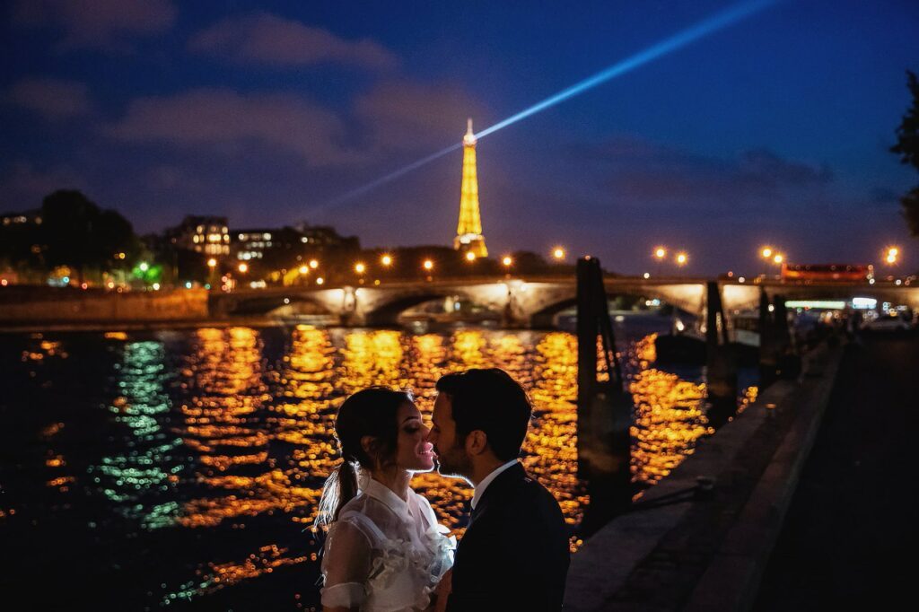 portrait of married couple at night with tour eiffel and seine river on background