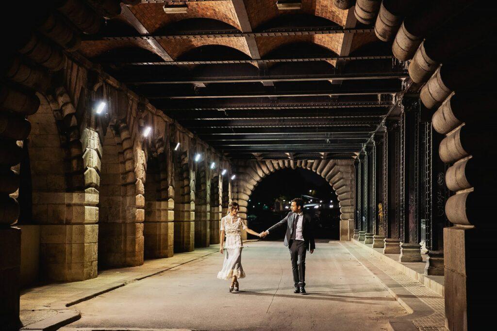 bride and groom walking under the bridge at night after their wedding in paris