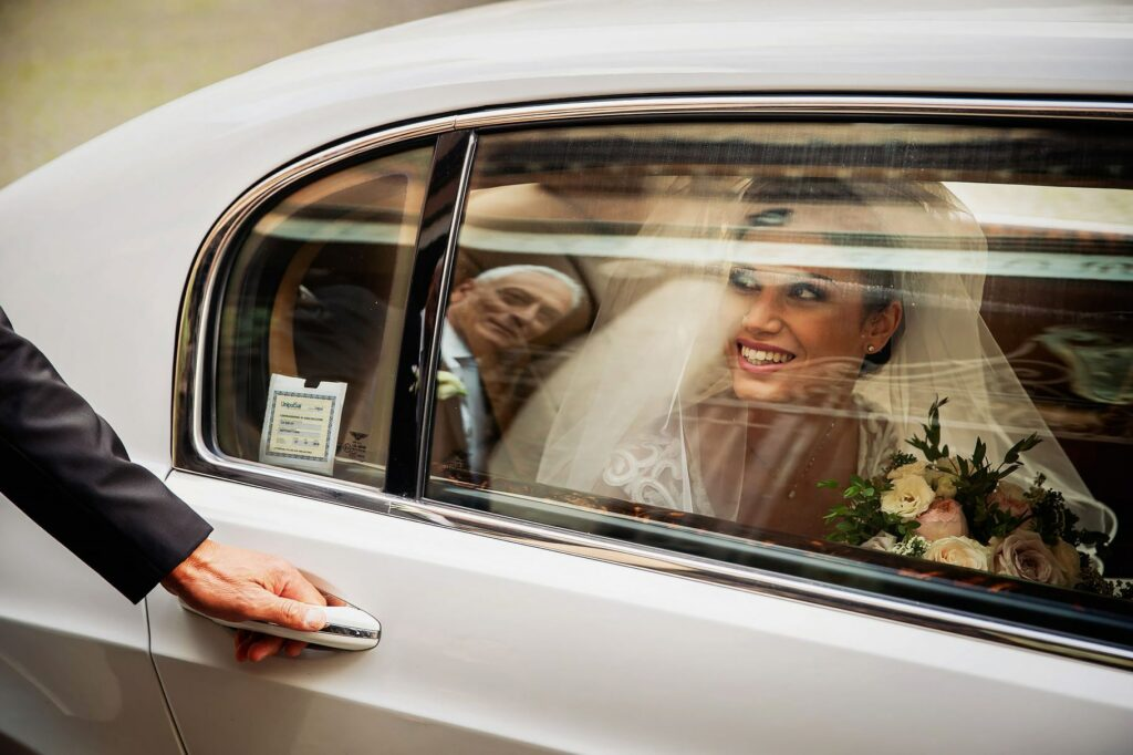 the bride arrives in front of the church and her father opens the car door for her