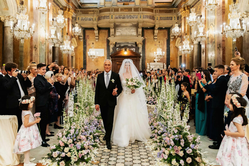 bride is entering into the church of the chandeliers for the wedding of a football player