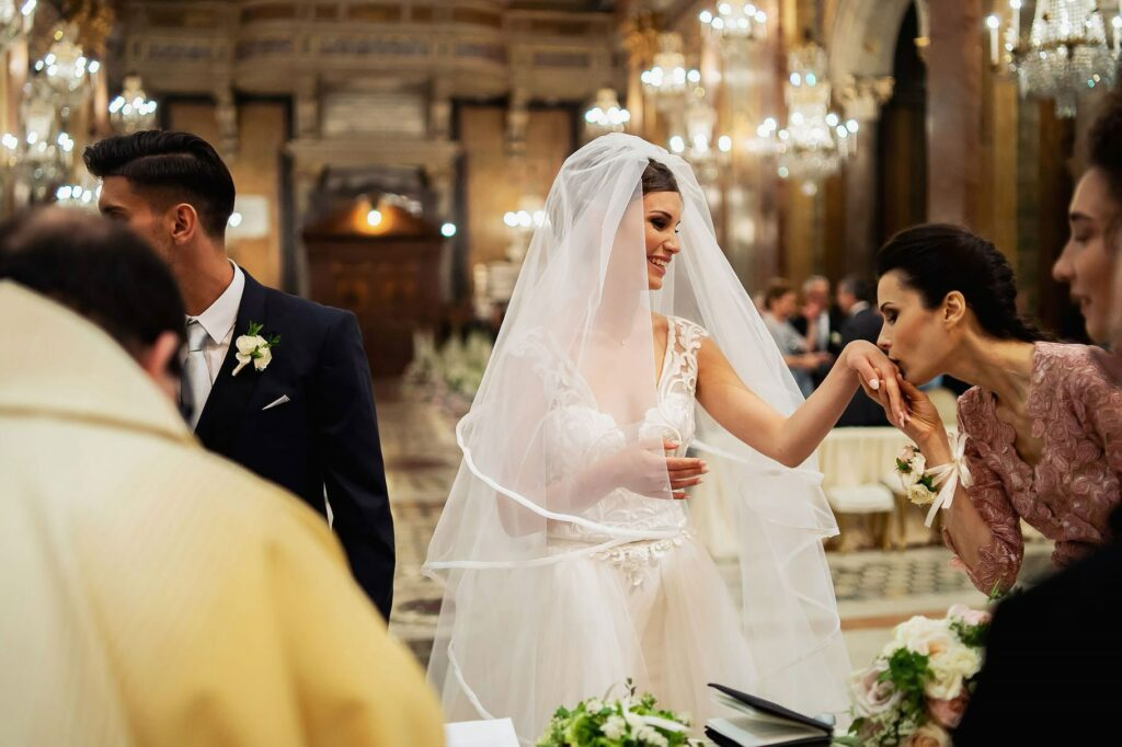 bridesmaid kisses the bride ring at the wedding of a football player