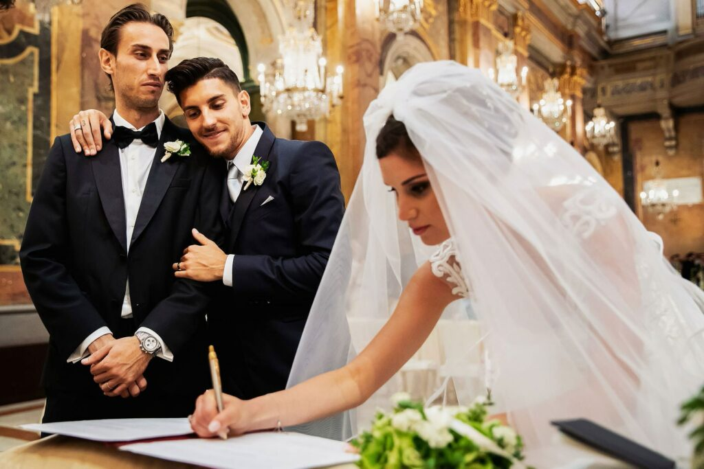 bride signing the wedding register while the groom and the best men two football player hugging
