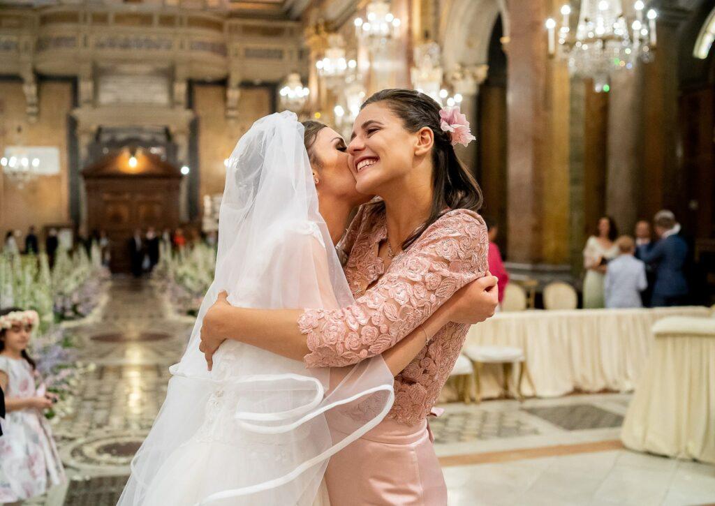 bride hugging bridesmaid at the end of wedding ceremony