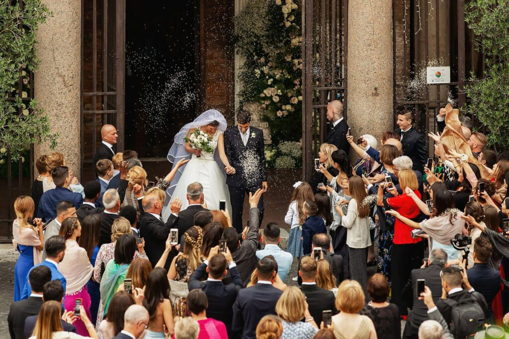 bride and groom exiting the church with all the guests throwing rice and confetti to them