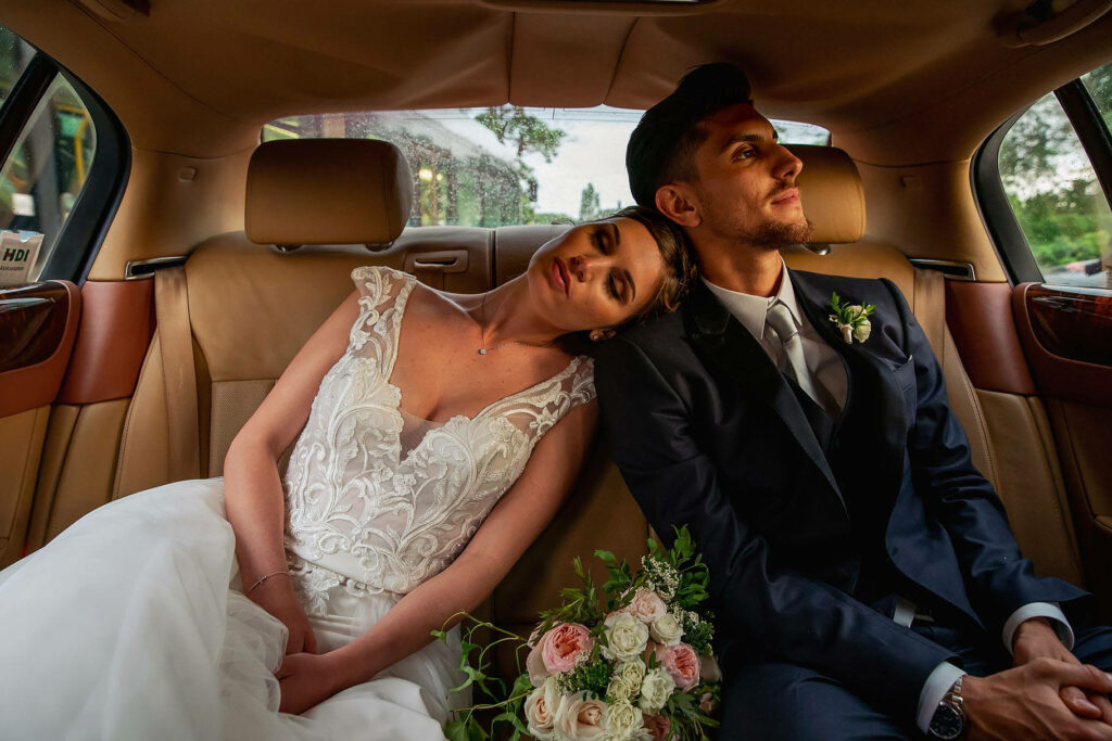 the groom and the bride in the car tired after the wedding of a football player