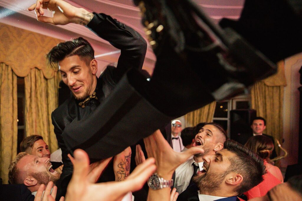 the groom thrown into the air during lorenzo pellegrini wedding party