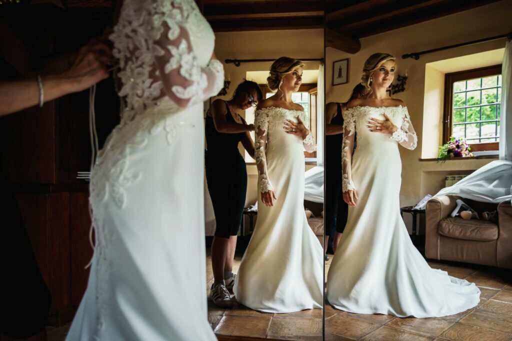 bride wearing the wedding dress at the mirror