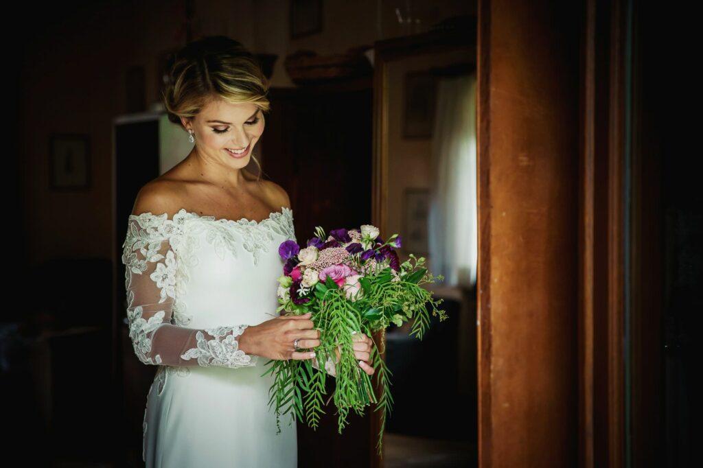 bride admiring her bouquet ready for kledi kadiu wedding