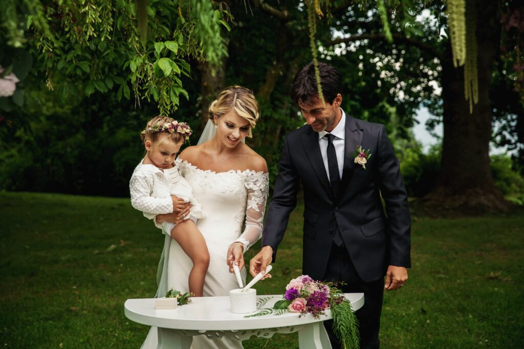 bride groom and their daughter at wedding ceremony lighting up candles