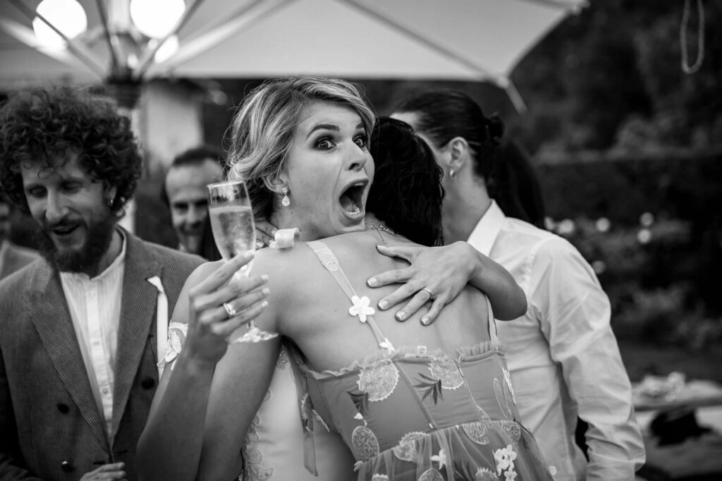 bride with a funny expression hugging a friend