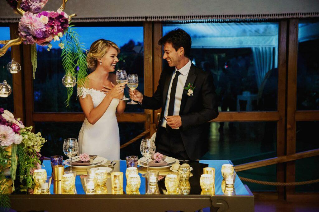 toast between bride and groom at the table during kledi kadiu wedding dinner