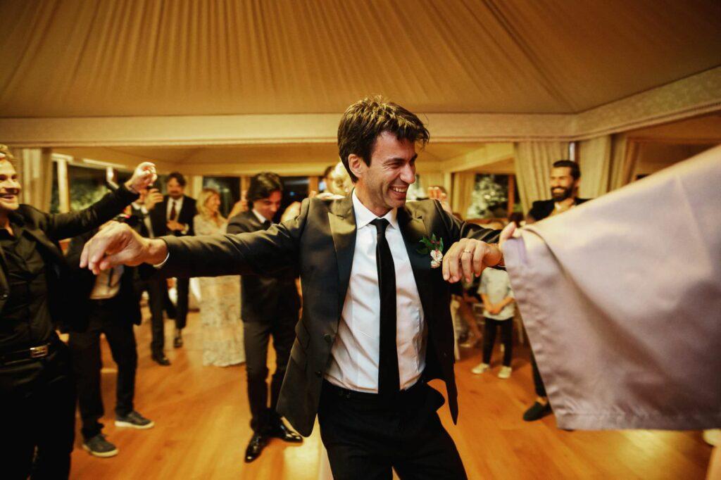 groom engaging a folk dance at wedding reception
