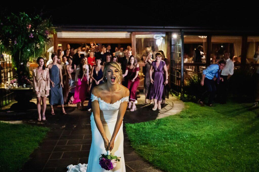 bride throwing bouquet at kleli wedding reception