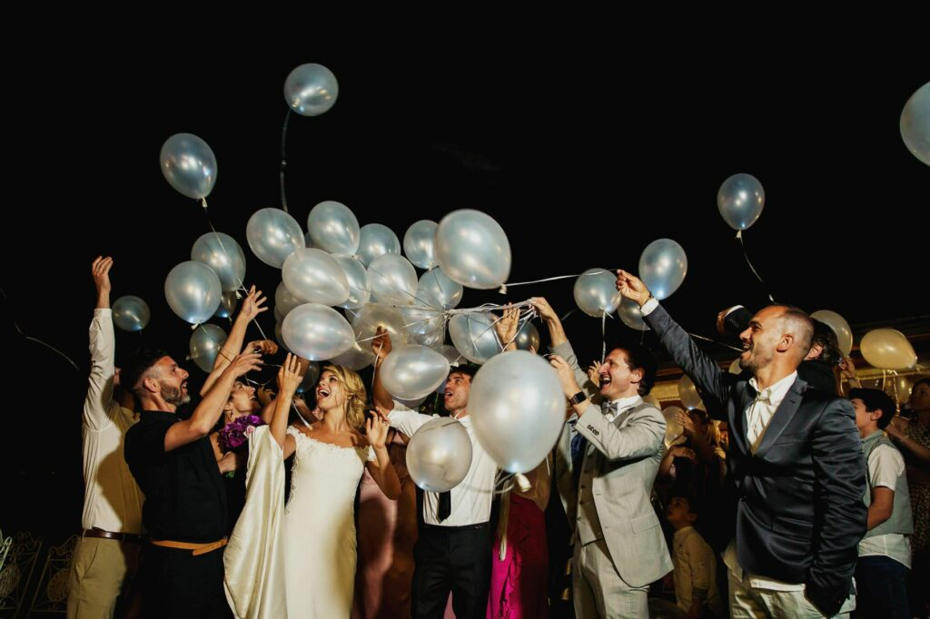 bride groom and guests throwing light balloons