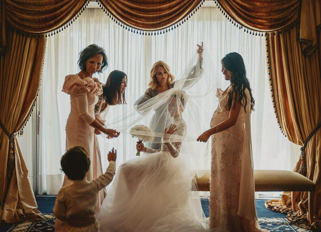 bride wearing veil helped by bridesmaids in the elegant rome cavalieri hilton hotel in rome