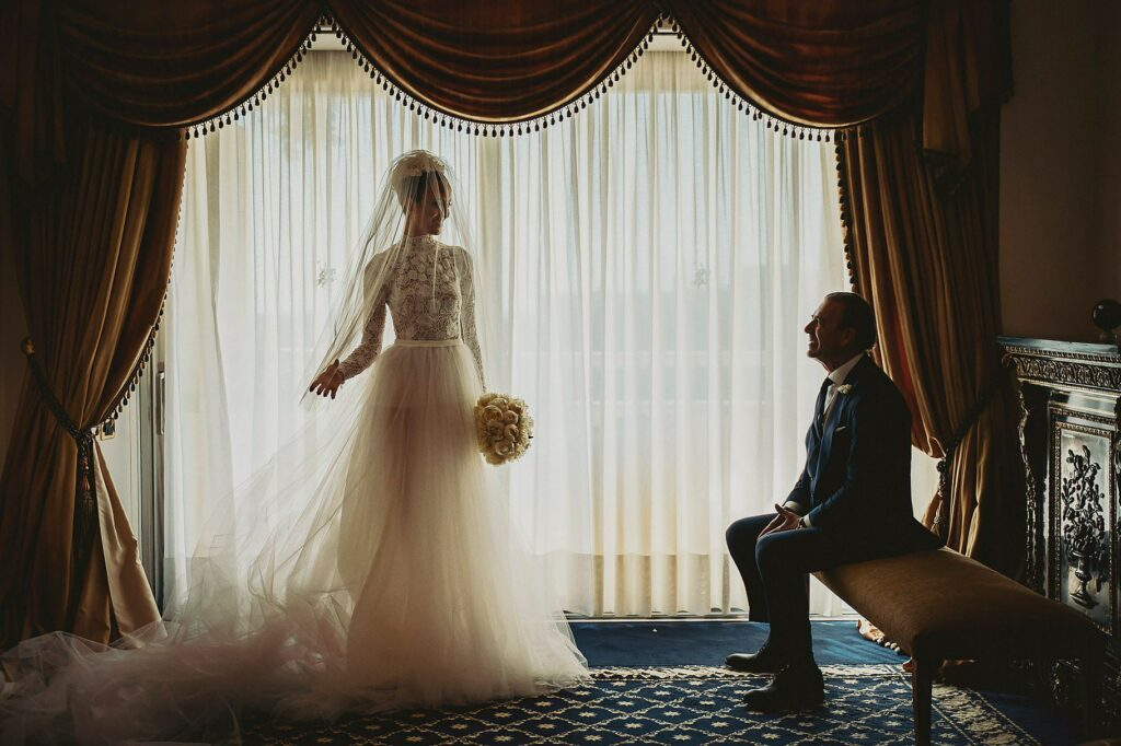 bride is just dressed and her father stares at her with wonder before the spanish-italian wedding at Villa Miani