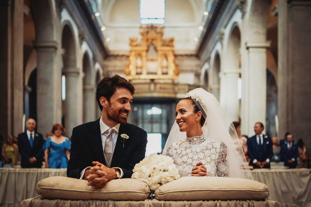 bride and groom looking at each other and smiling during the spanish-italian wedding ceremony