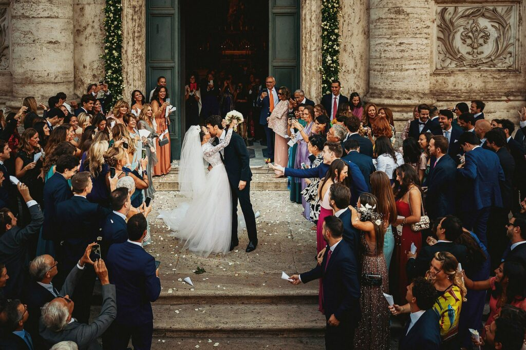 bride and groom exit from the church and kiss each other at confetti throwing