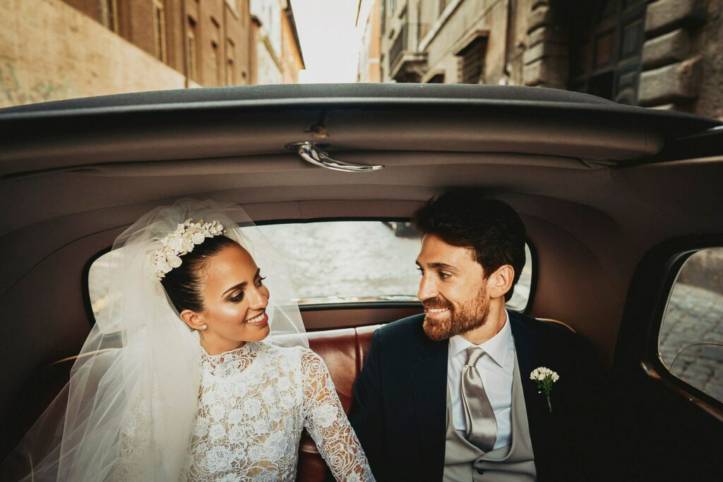 the happy couple in the car after the Italian-Spanish wedding