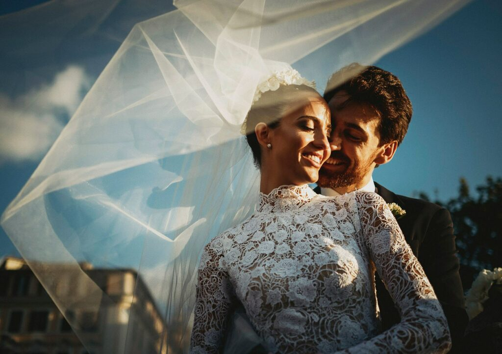 photo portrait of a bride and groom with the bride veil lifted by the wind