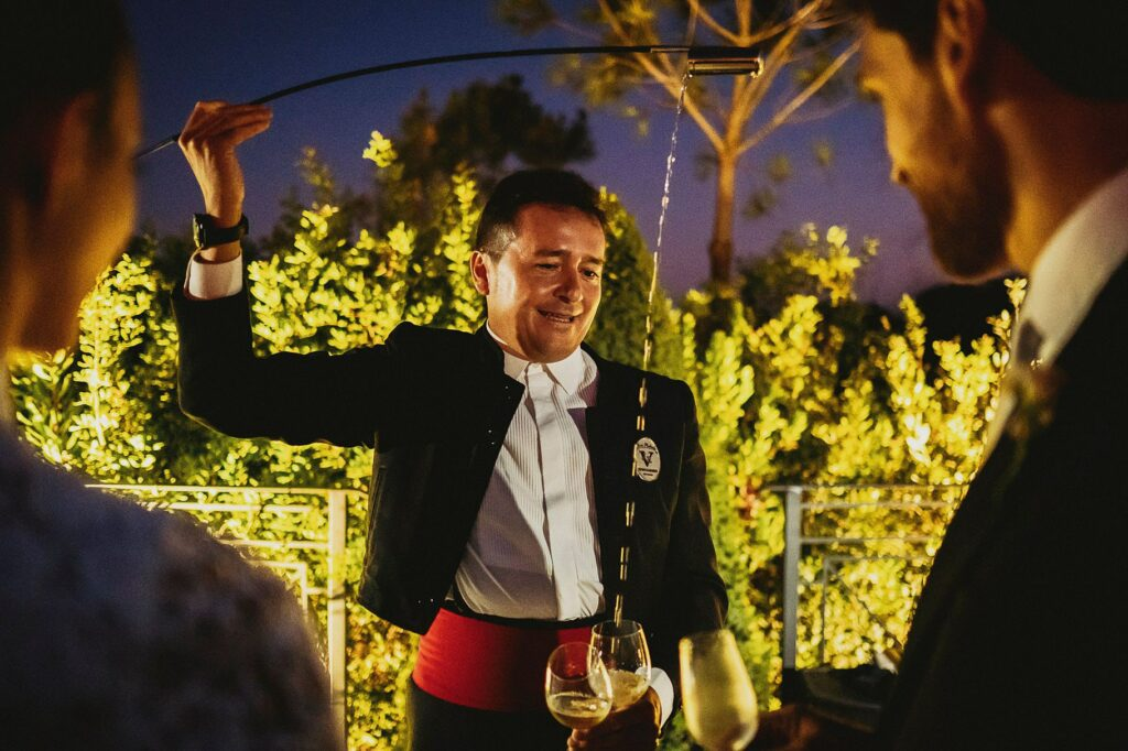 bride and groom looking at the sommelier and his choreographic wine pouring during the spanish-italian wedding reception