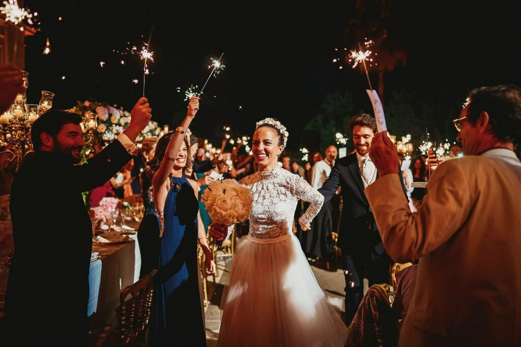 entrance of the bride and groom into the reception hall with the guests waving sparkles