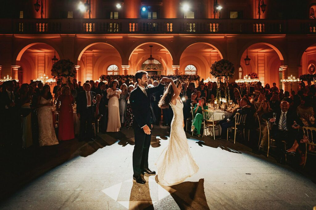 the bride and groom in the spotlight for their first dance at the wedding reception