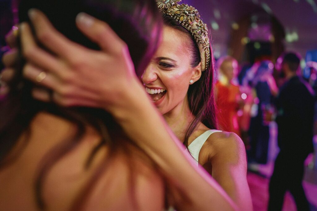 the radiant bride hugs a friend during the dance party at the italian-spanish wedding at villa miani